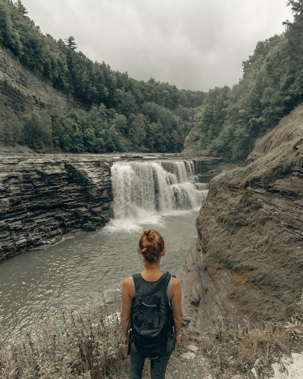 woman in black tank top sitting on rock near waterfalls during daytime