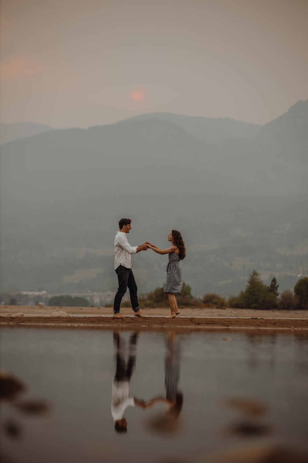 man and woman kissing on brown field near lake during daytime