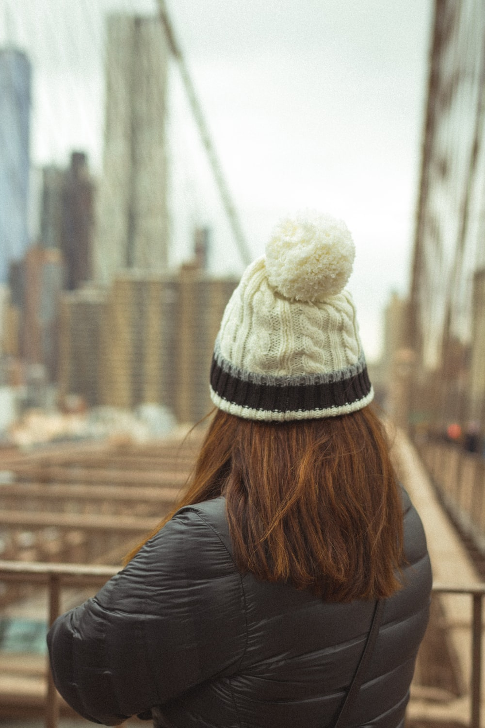 woman in black jacket and white knit cap
