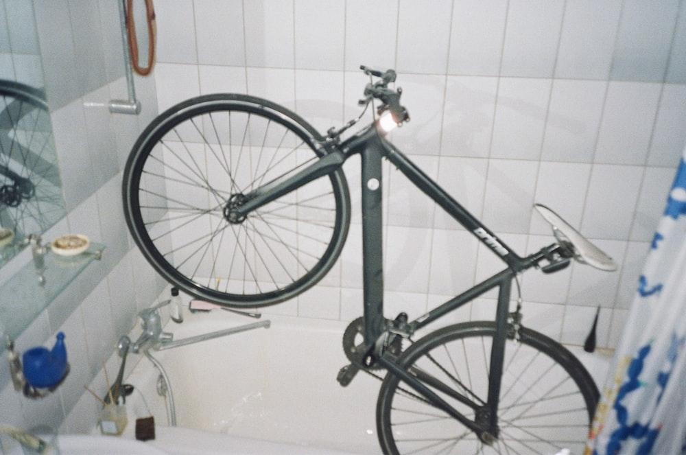 black and gray bicycle on white ceramic bathtub