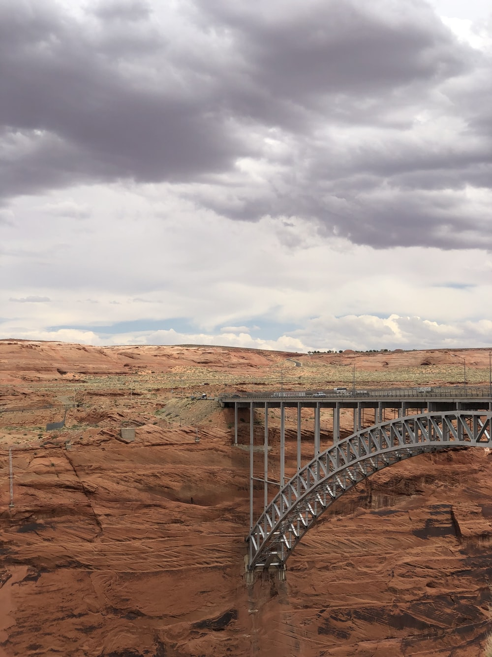gray metal bridge over brown rock formation under white clouds during daytime