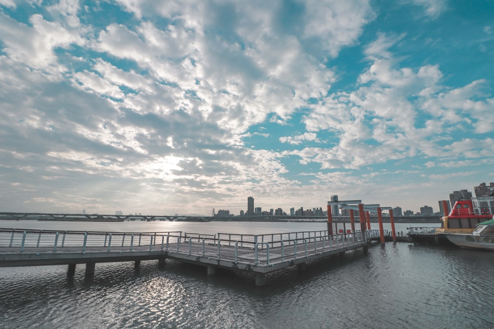 gray wooden dock on body of water under blue and white cloudy sky during daytime