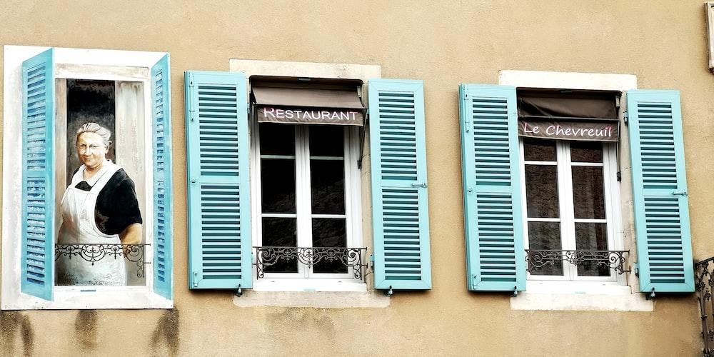 blue wooden window on beige concrete wall