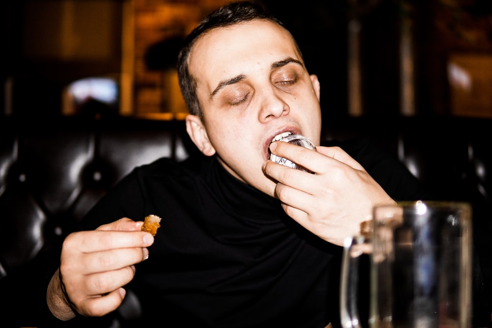 man in black crew neck shirt eating bread