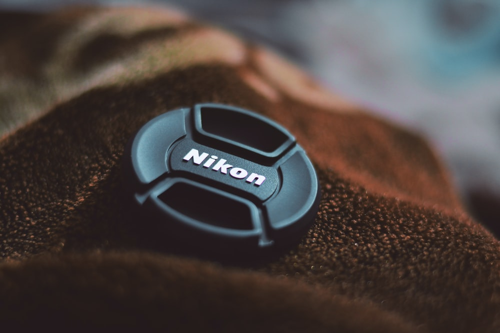 black nikon camera lens cover on brown textile