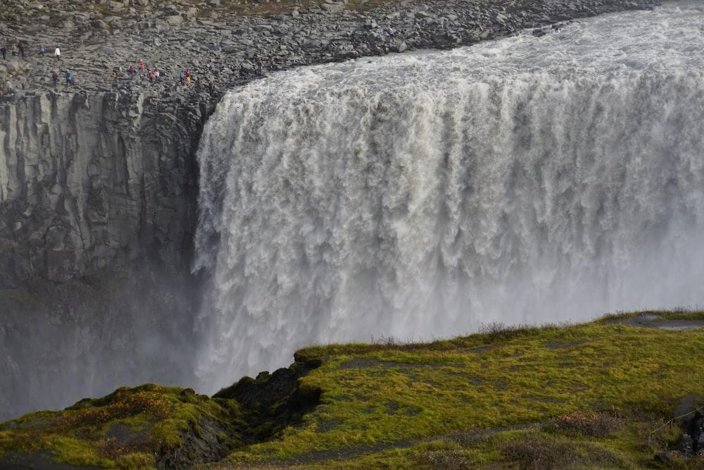 waterfalls on green grass field during daytime