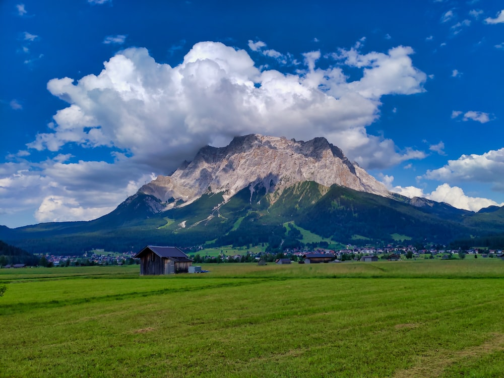 brown wooden house on green grass field near mountain under white clouds and blue sky during