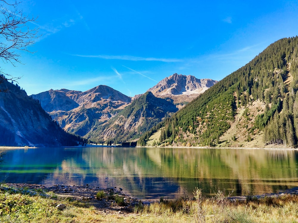 green and brown mountains beside lake under blue sky during daytime