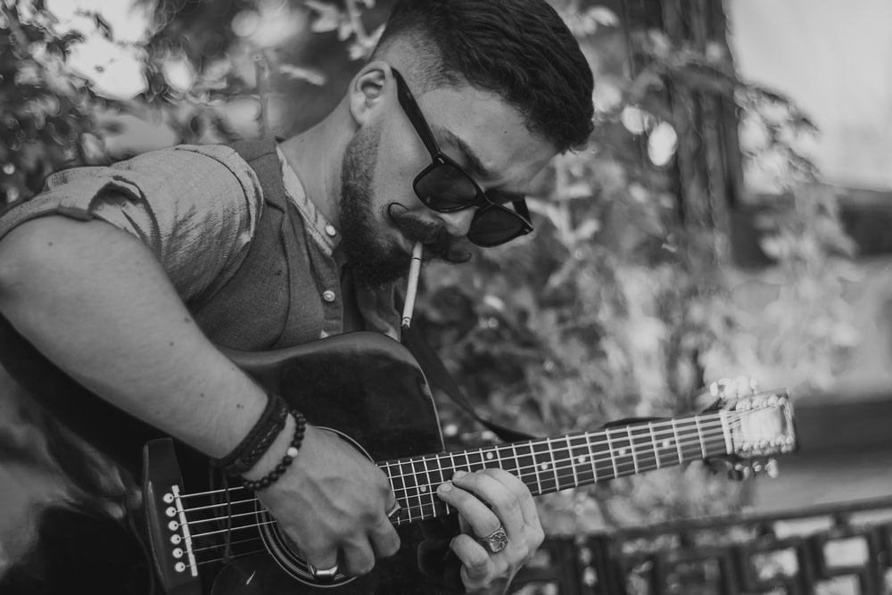 man playing acoustic guitar in grayscale photography