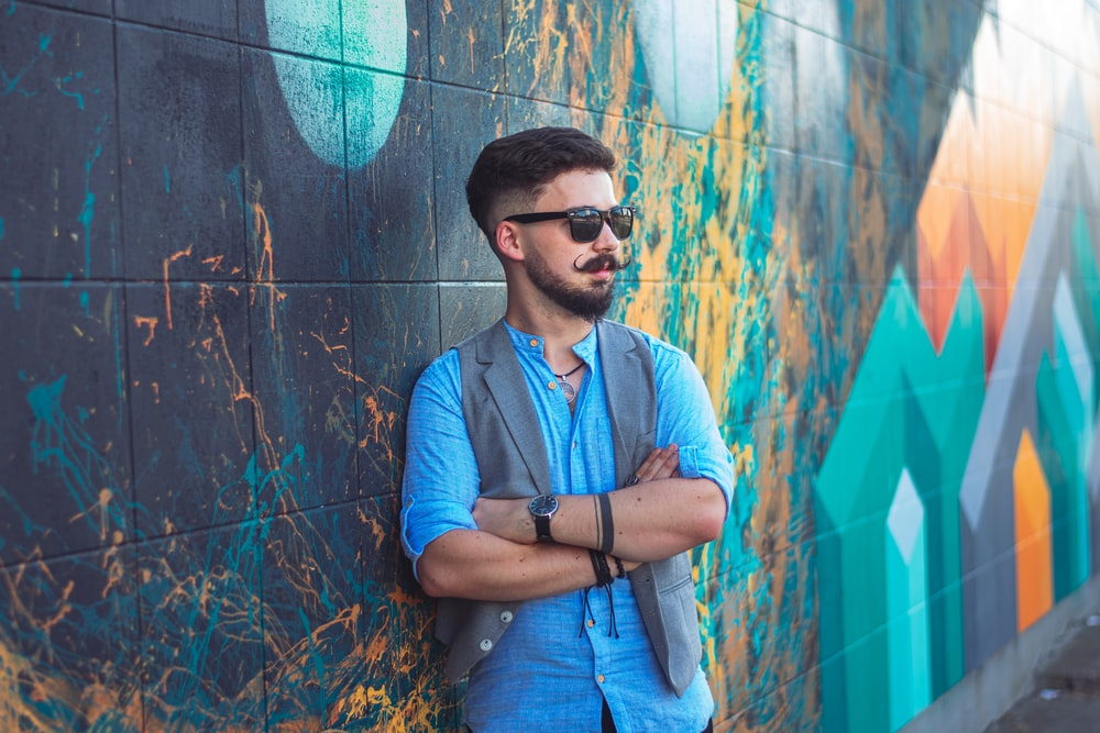 man in blue button up shirt wearing black sunglasses