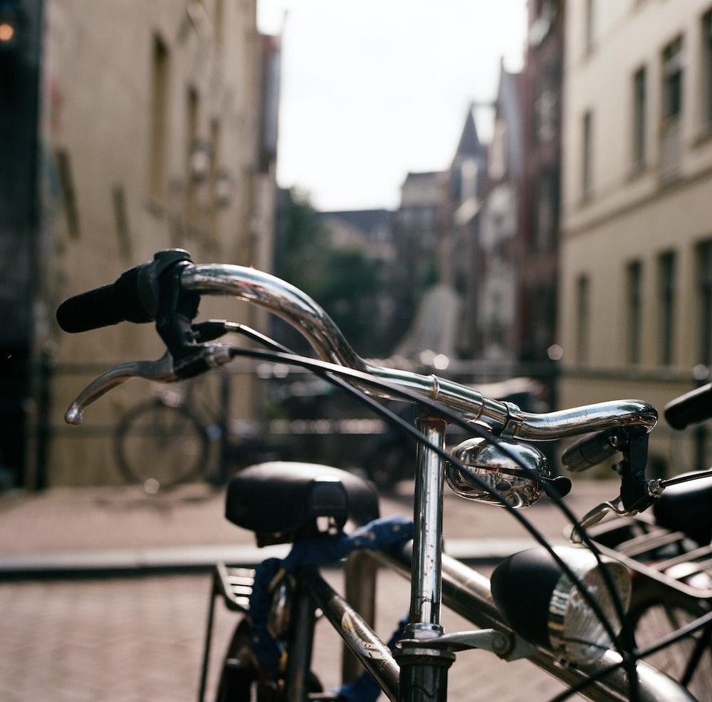 black city bike parked on sidewalk during daytime
