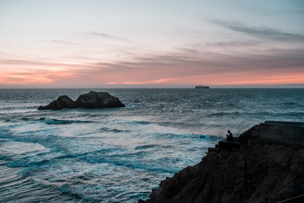 people standing on rock formation near sea during sunset