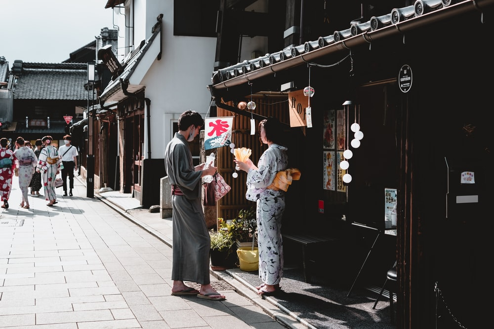 man and woman standing on sidewalk during daytime