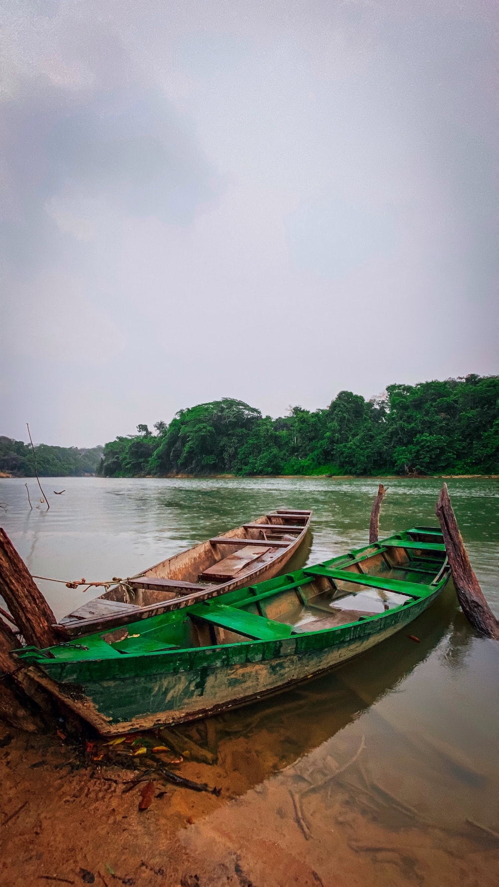 green and brown wooden boat on body of water during daytime
