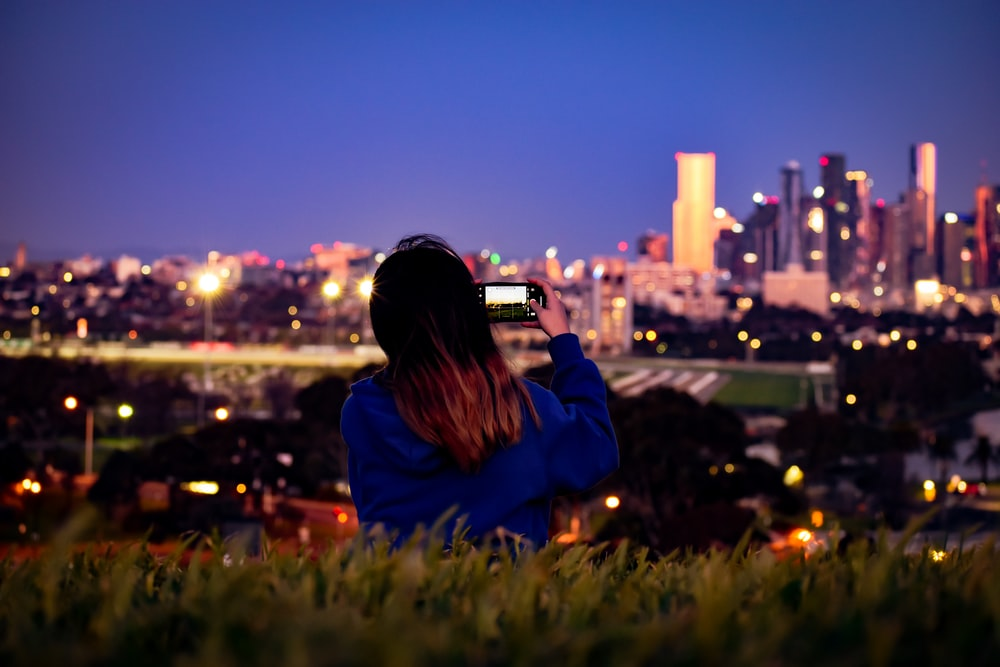 woman in blue jacket standing on green grass field during night time