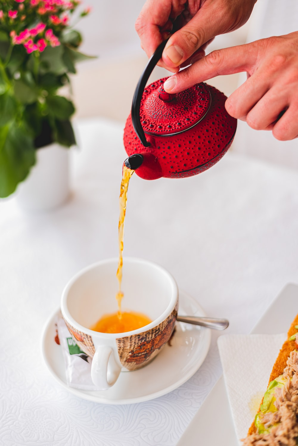 person pouring red liquid on white ceramic teacup