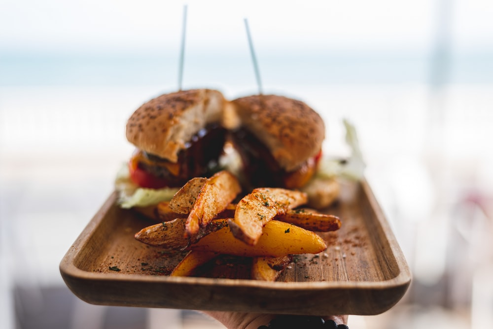 burger with patty and cheese on brown wooden tray