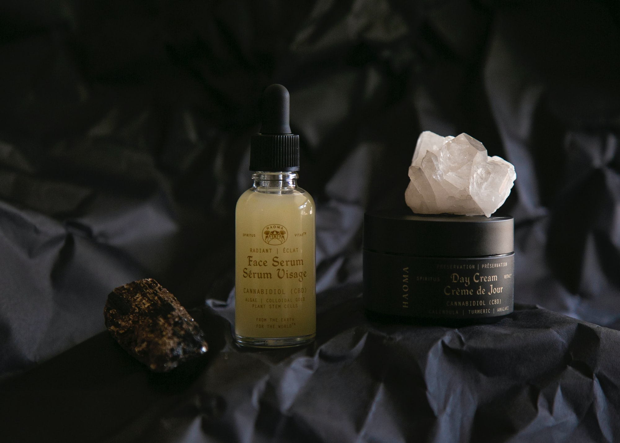 Face serum and day cream from Haoma, an organic skin care line of products surrounded by clear quartz and black tourmaline crystals.