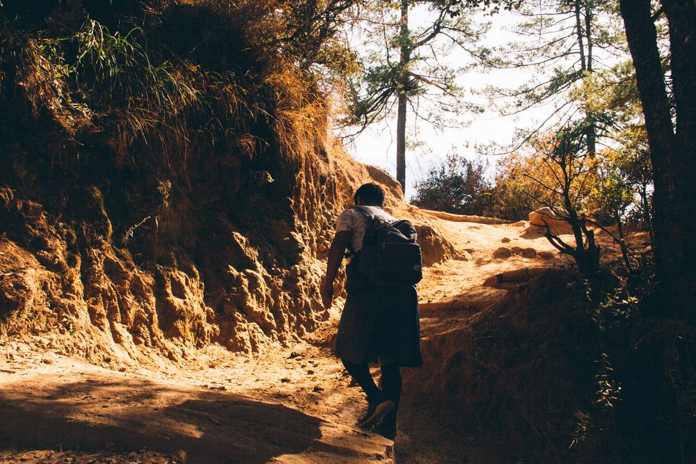 man and woman walking on brown dirt road during daytime
