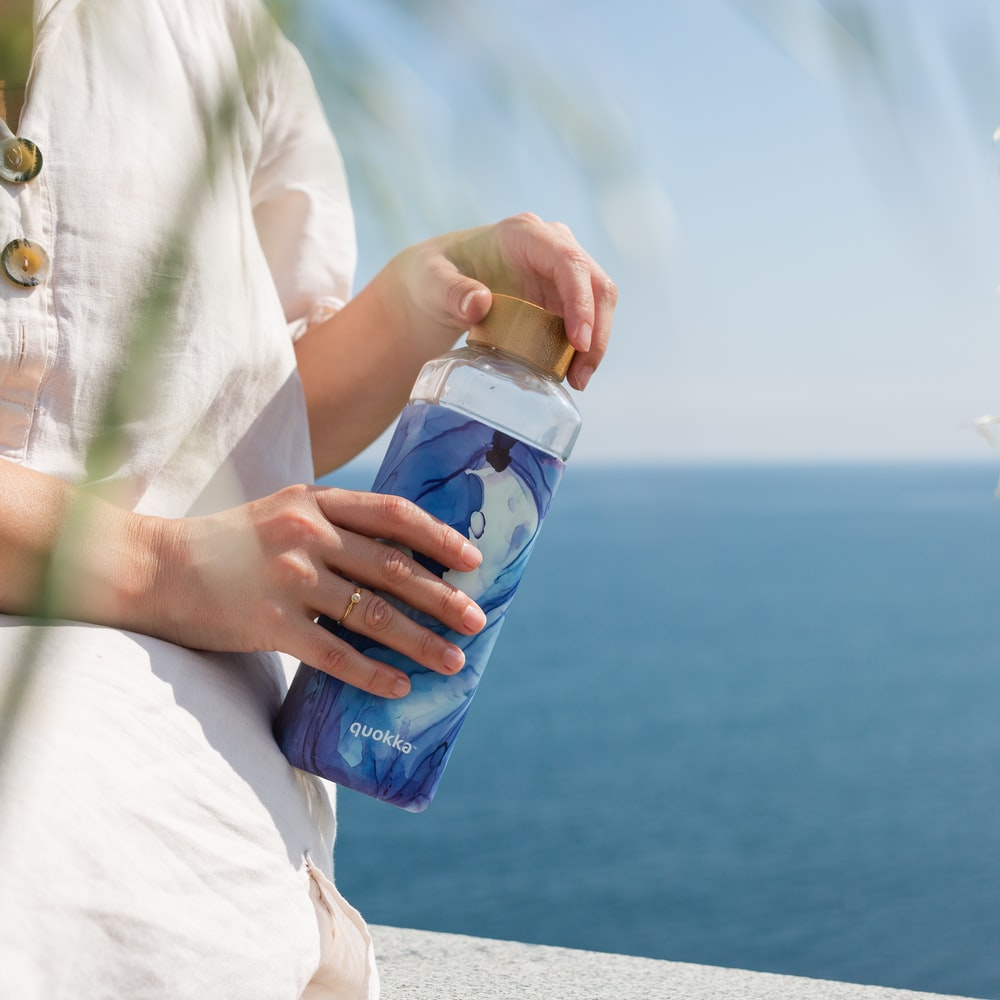 person in yellow button up shirt holding blue and white plastic bottle