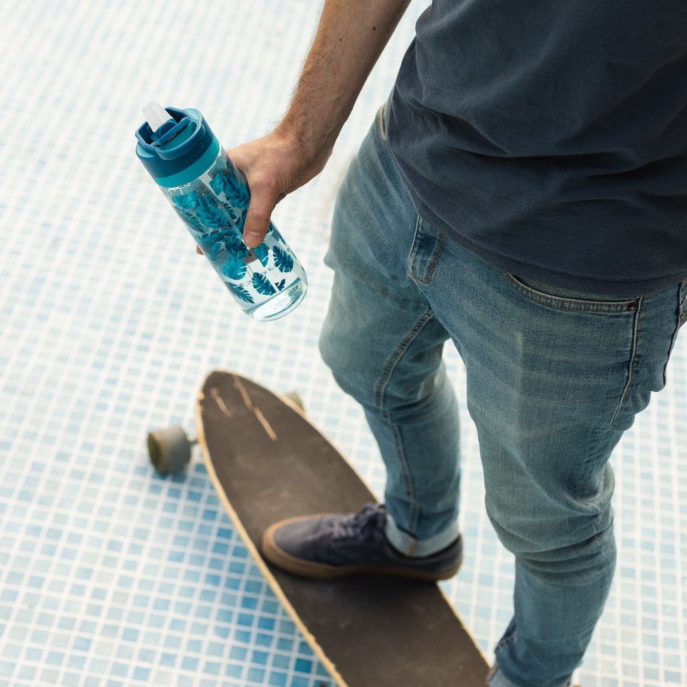 man in white button up shirt and blue denim jeans holding orange and white labeled bottle