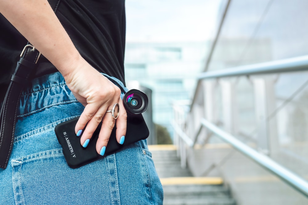 person in black t-shirt and blue denim jeans holding black dslr camera