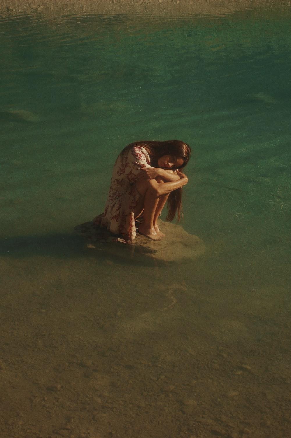 woman in black bikini lying on water