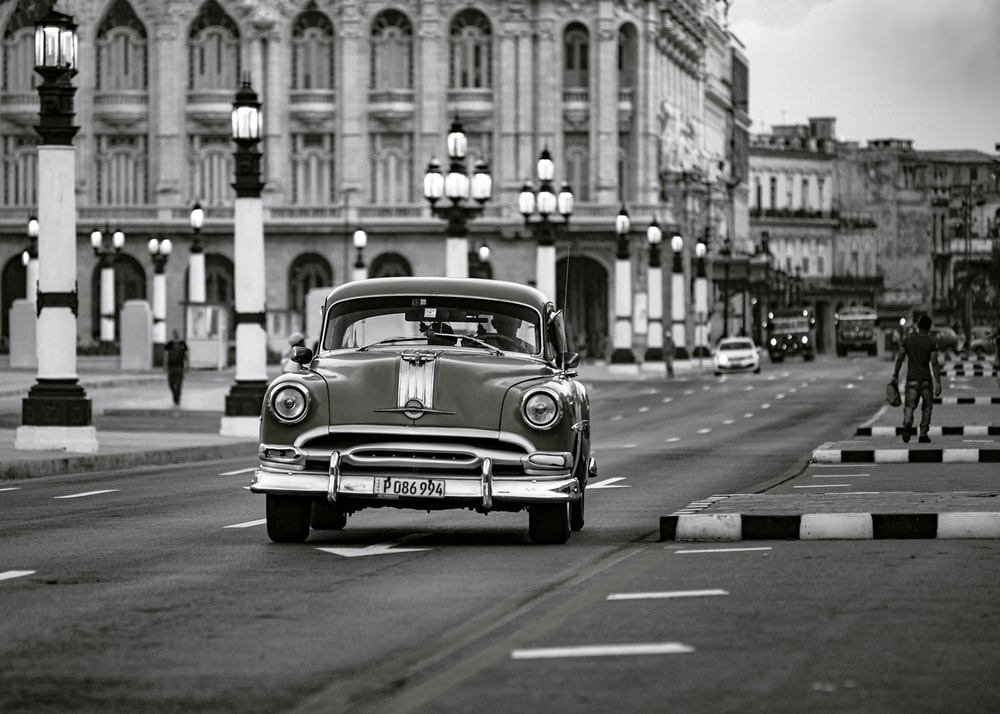 grayscale photo of classic car on road