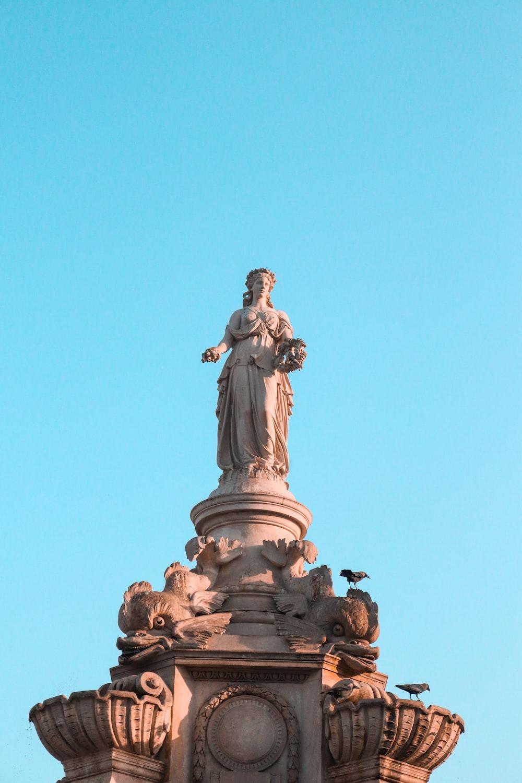 man in robe statue under blue sky during daytime