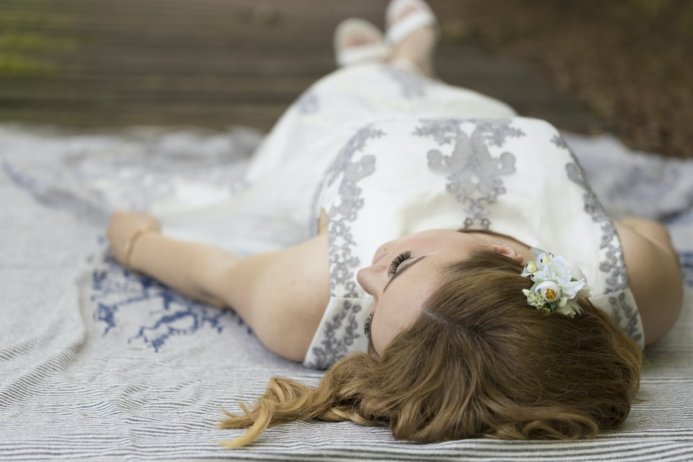 woman in white floral dress lying on white textile