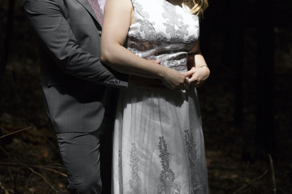 man in black suit jacket beside woman in white floral dress