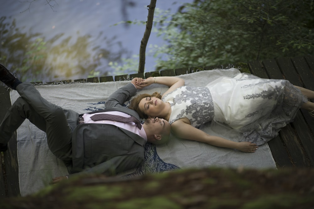woman in white and black floral dress lying on gray hammock