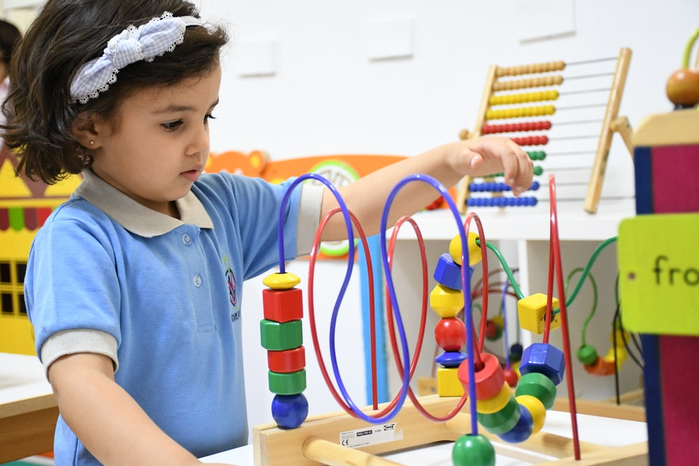 boy in blue polo shirt playing with lego blocks