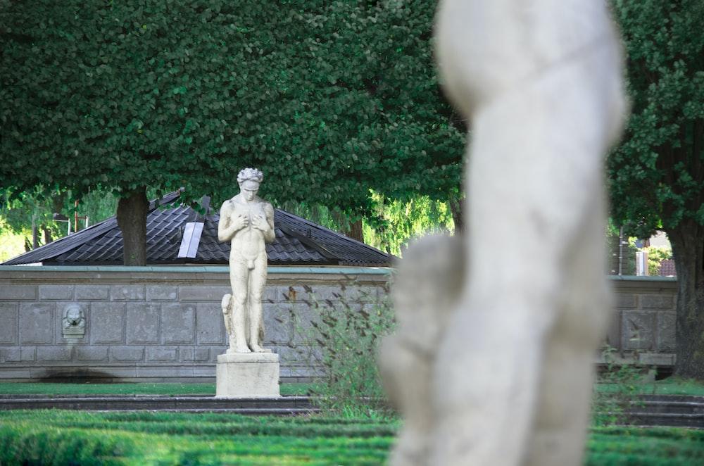 statue of man on green grass field