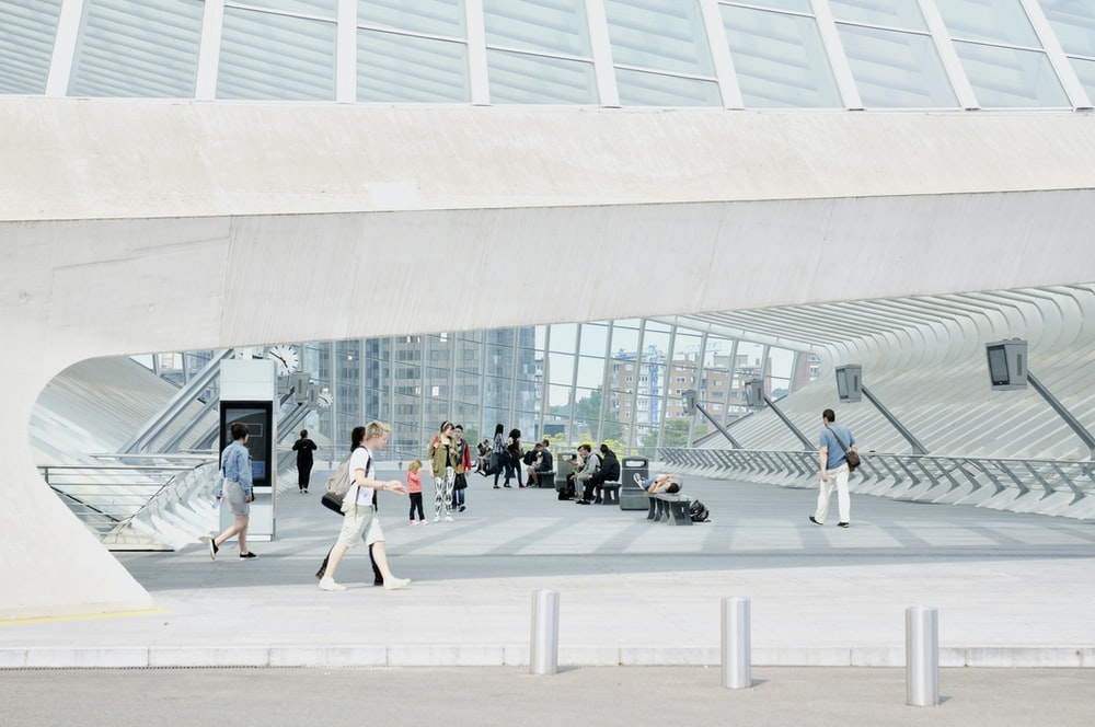 people walking on white concrete building during daytime