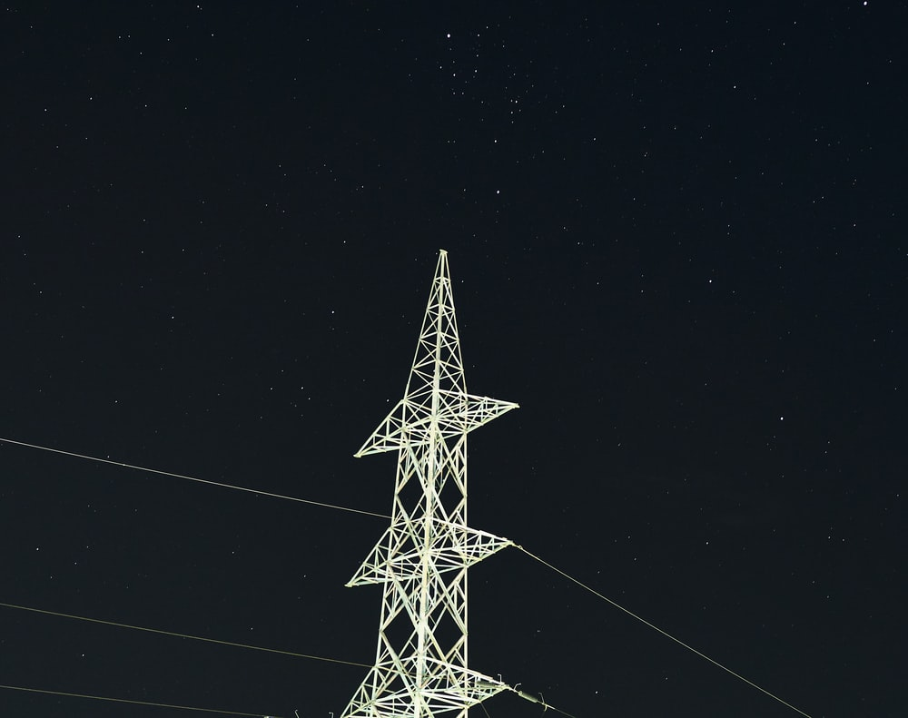 white and black electric tower during night time