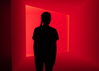 silhouette of woman standing in front of red wall