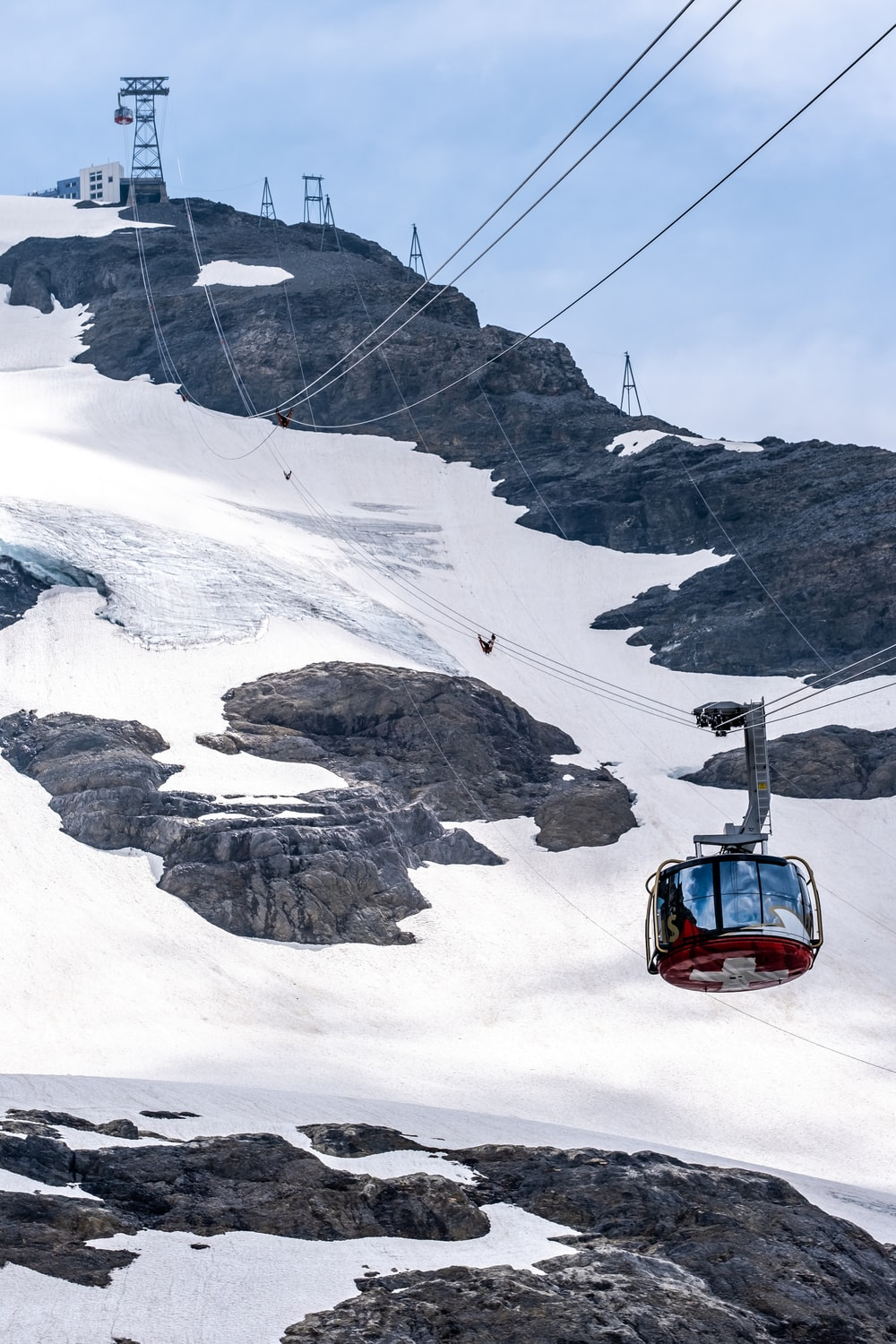 red car on snow covered mountain during daytime