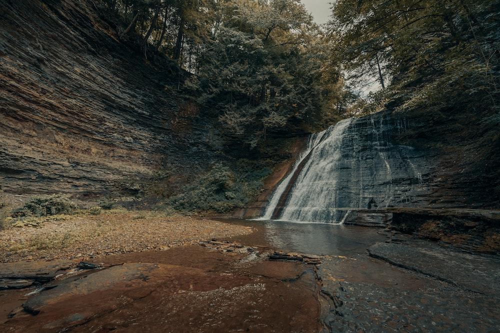 waterfalls in brown rocky mountain during daytime