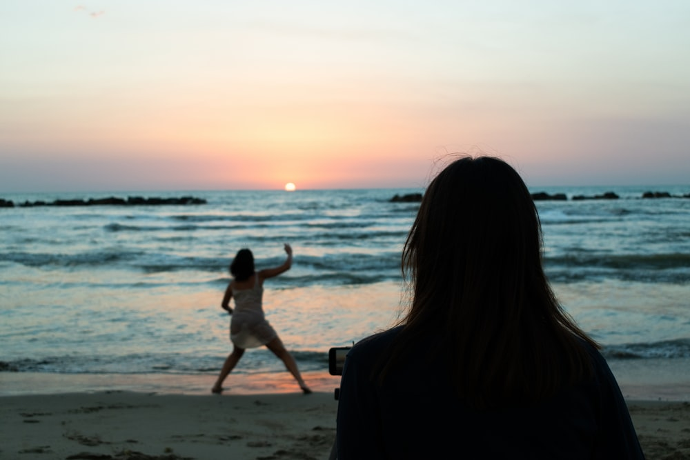woman in black dress holding a girl in white dress on beach during sunset