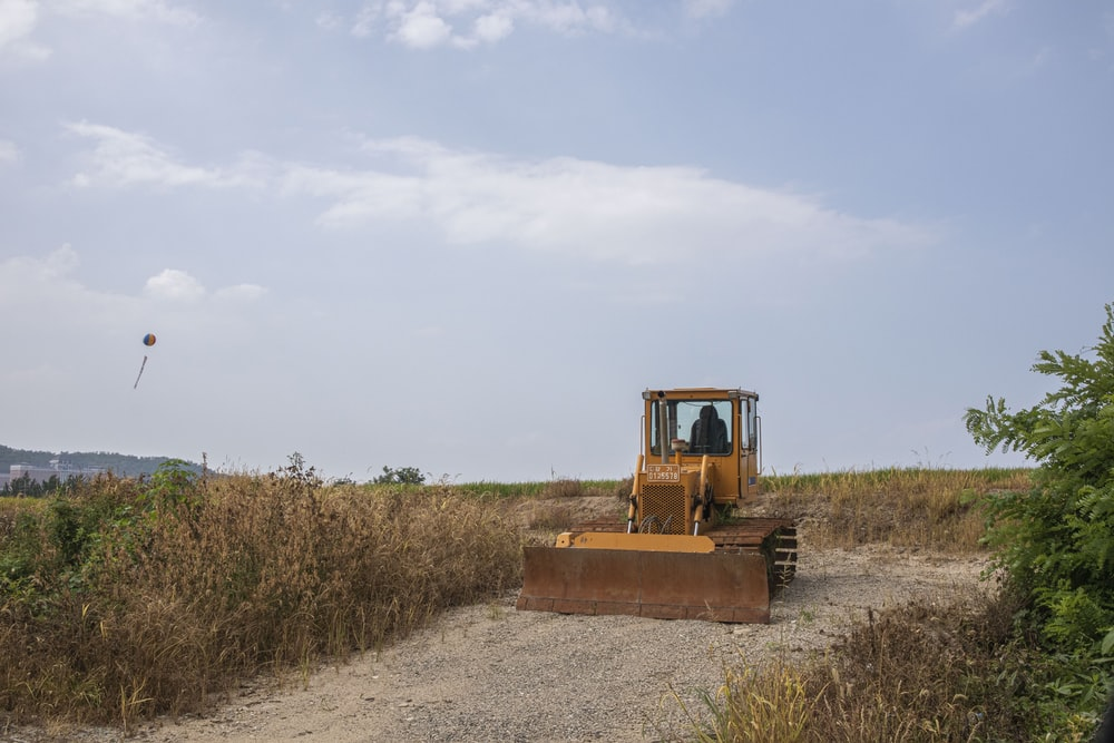 yellow and black heavy equipment on brown field under white clouds during daytime