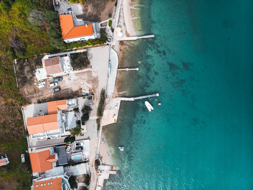 aerial view of houses near body of water during daytime