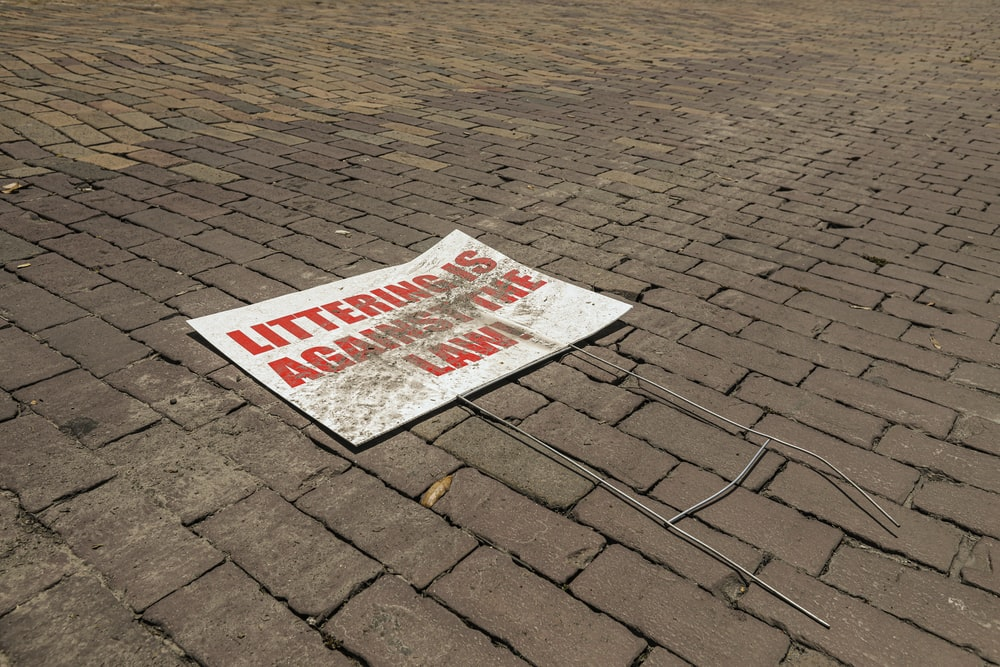 white and red no parking sign on brown brick floor
