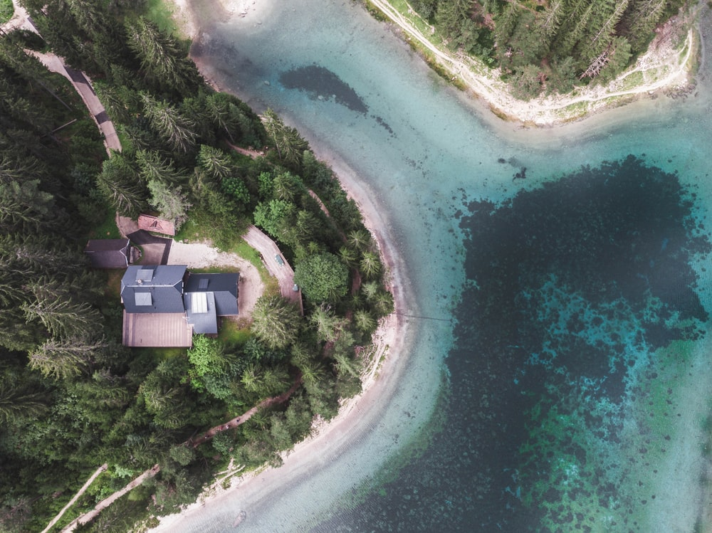 aerial view of house near body of water during daytime