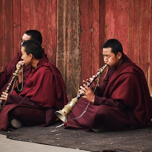 man in red robe playing flute