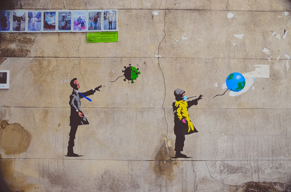 man in black and yellow jacket and black pants holding green and blue balloons
