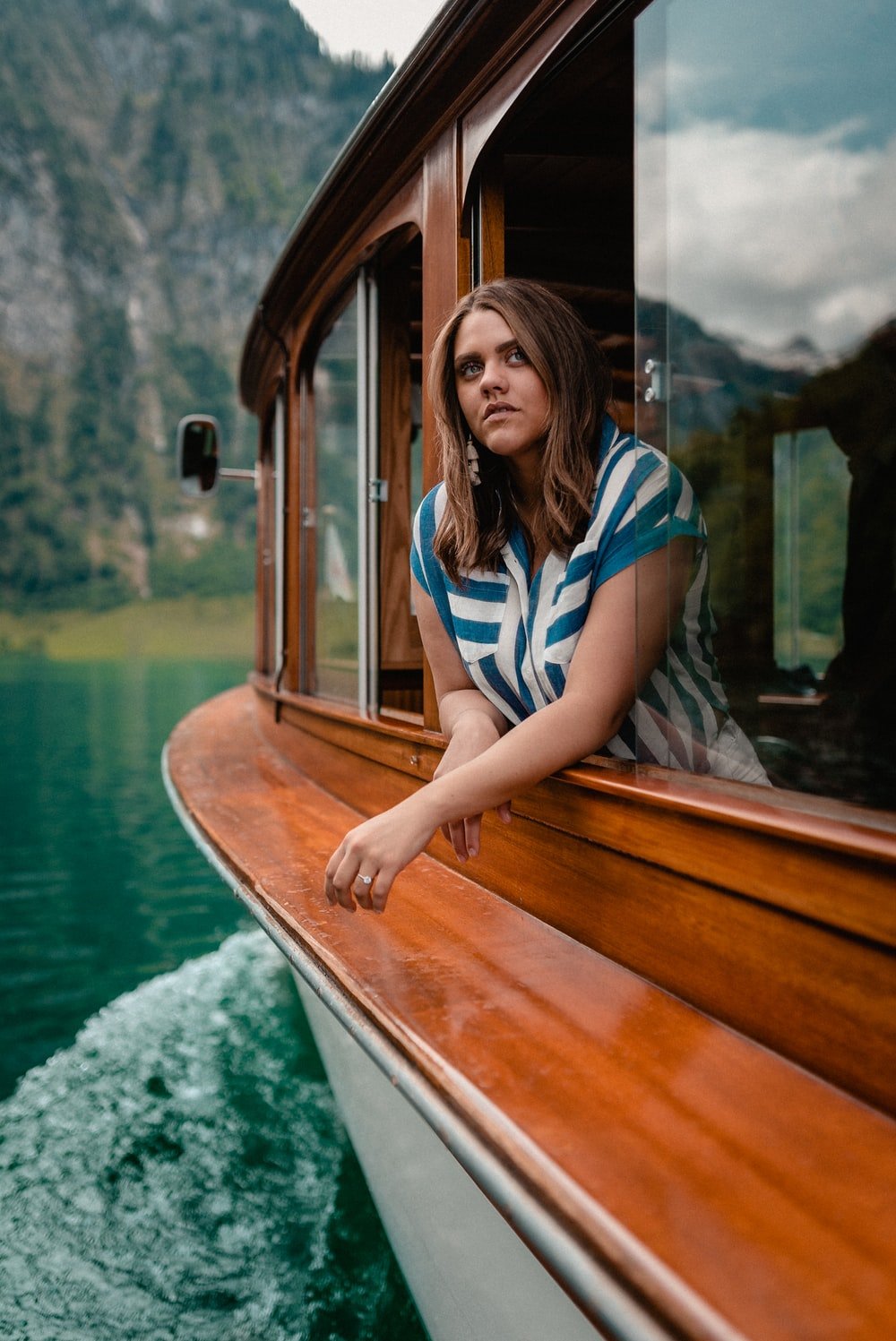 woman in blue and white stripe shirt sitting on brown wooden boat
