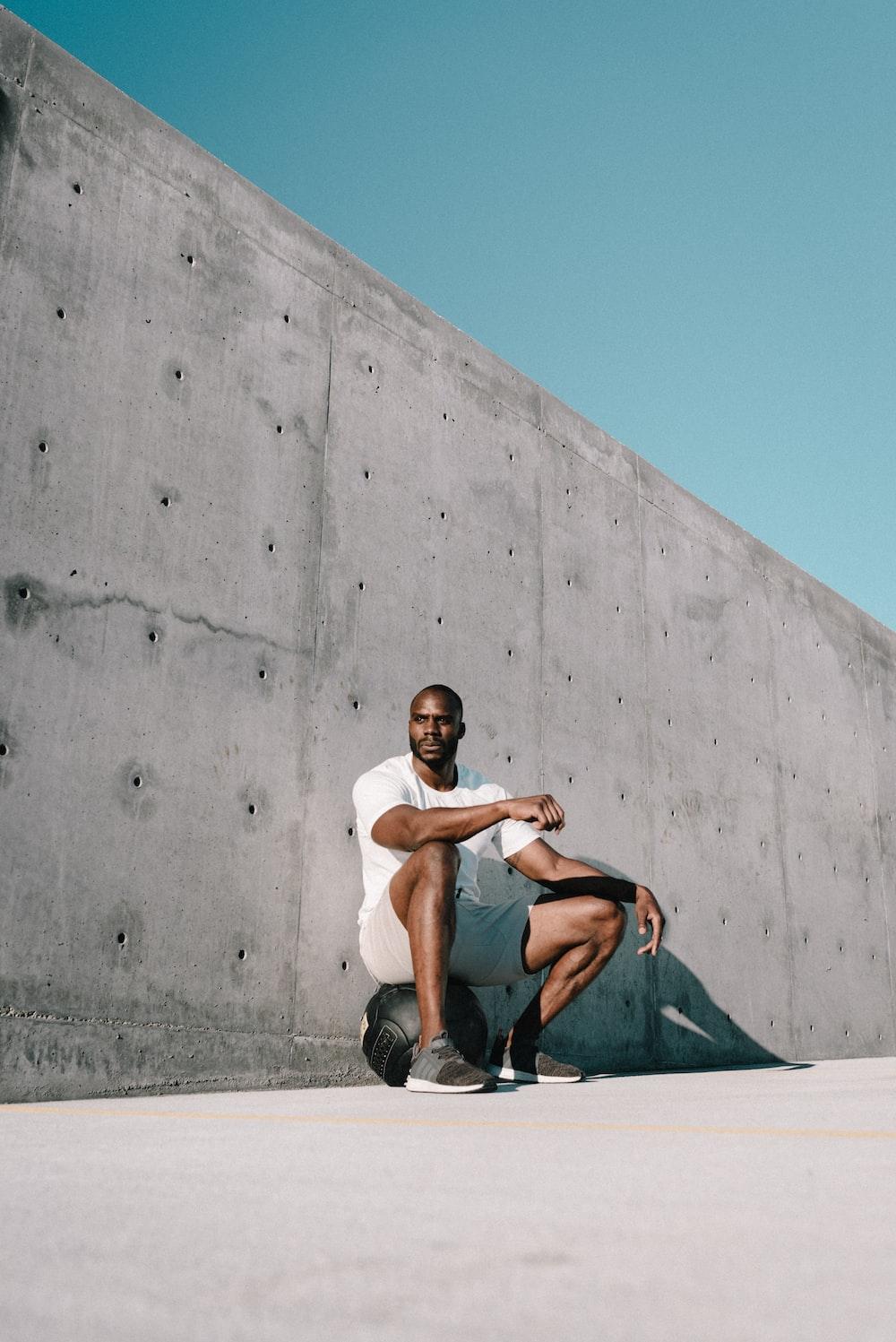 man in white t-shirt and black shorts sitting on black skateboard