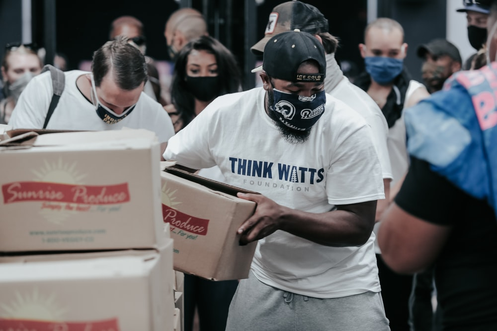 man in white crew neck t-shirt holding white box