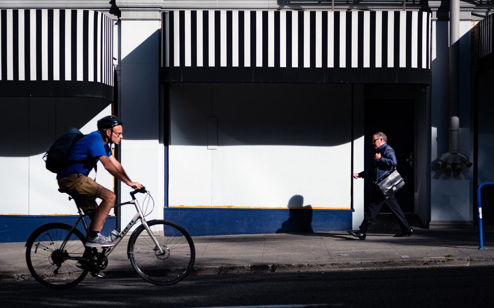 man in blue t-shirt riding on bicycle